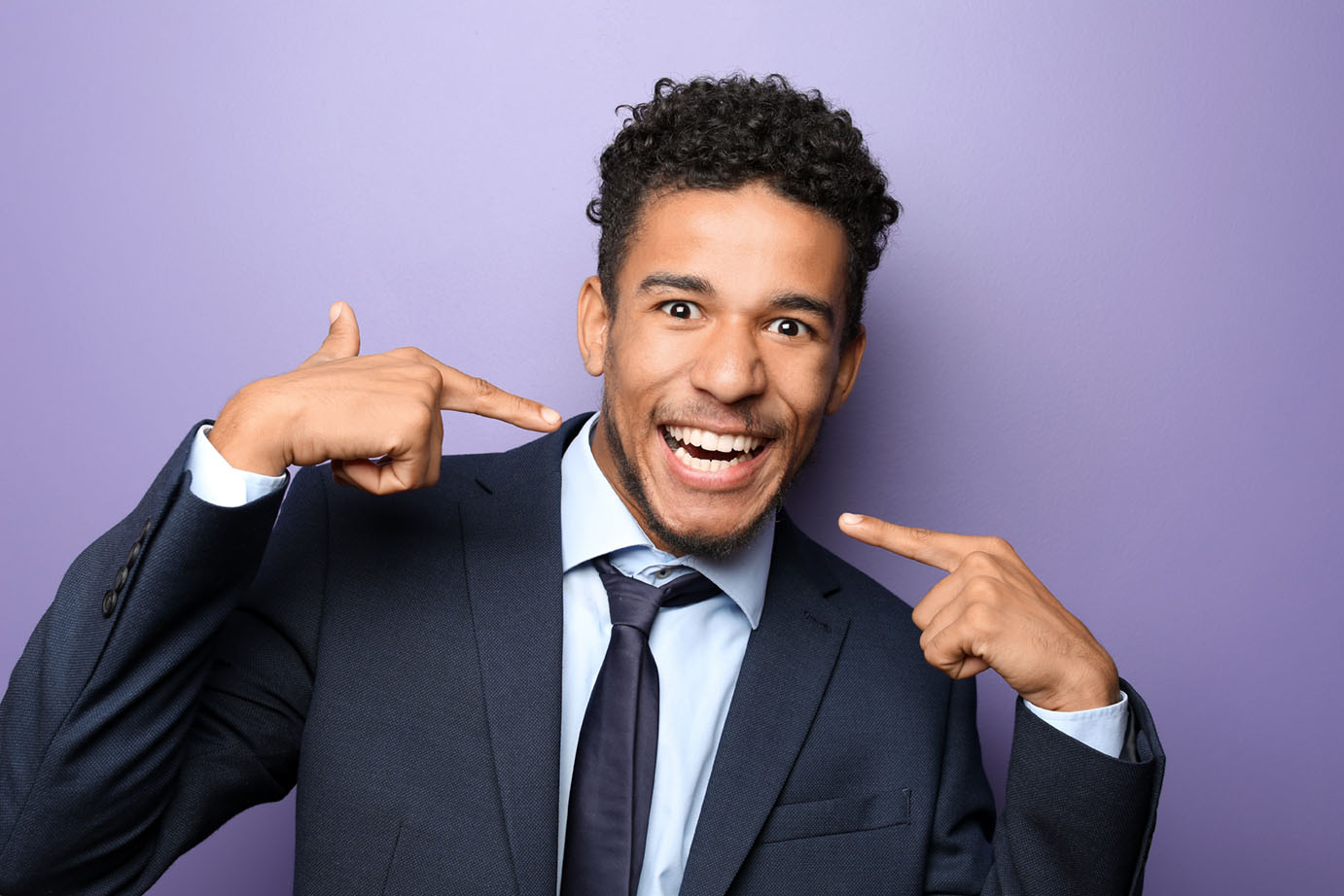 Portrait of happy African-American businessman on color background