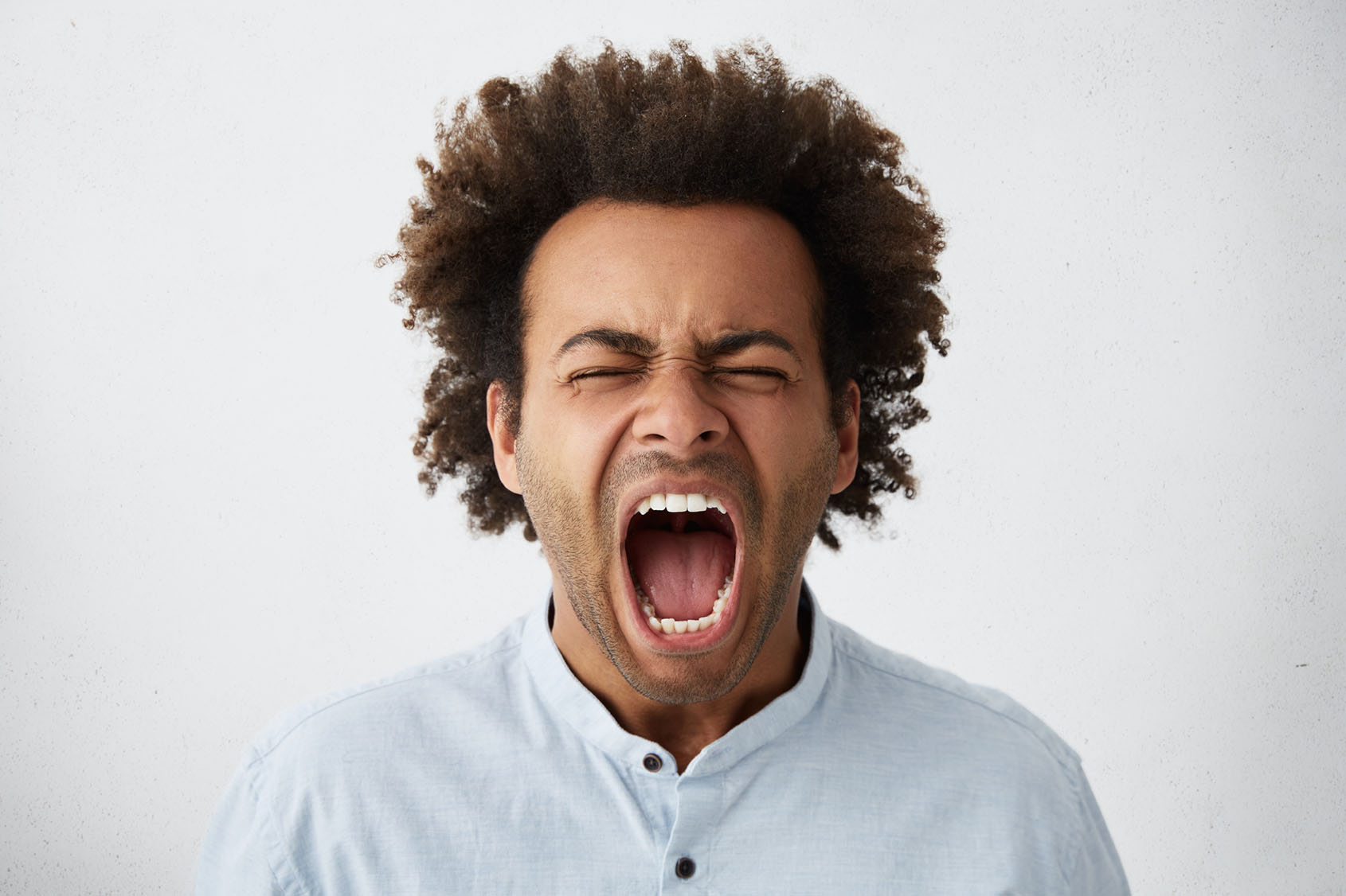 Close-up of Afro American man with bushy hair and pure skin having closed eyes and wide opened mouth screaming with great fear and anger. Furious dark-skinned male with curly hair shouting loudly
